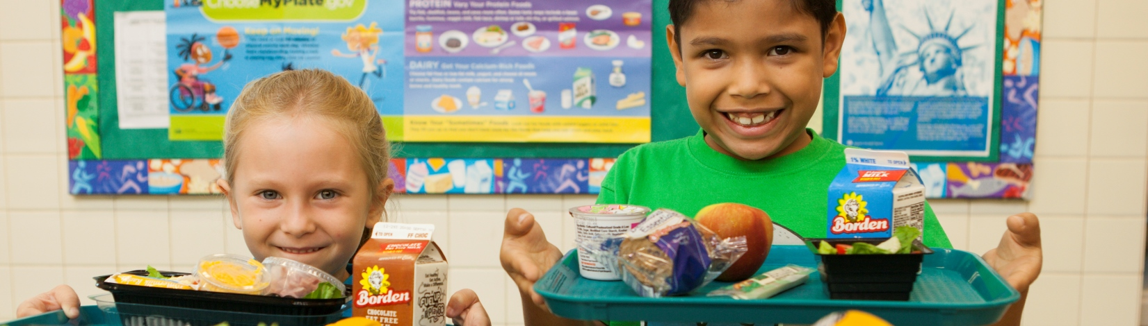 School children with healthy lunches on their trays