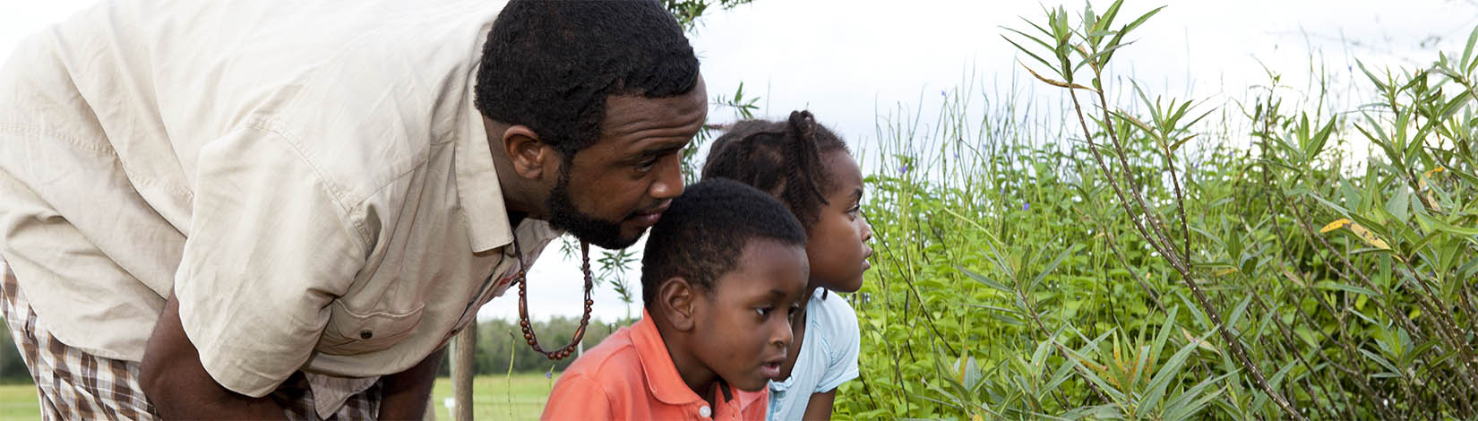 father and two children looking at plants
