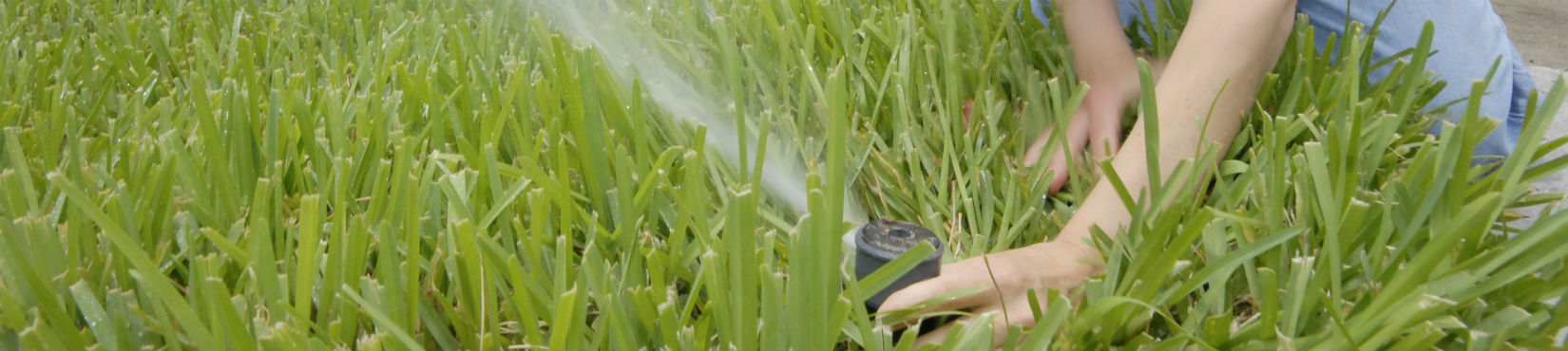 hands adjusting an irrigation rotor head in green grass