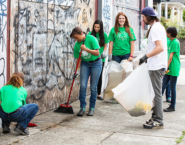 4-H youth cleaning a street with graffiti covered wall in background