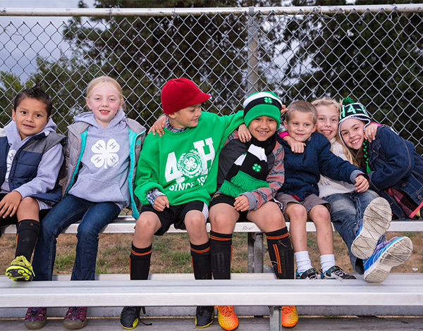 seven 4-H children sitting on a bench outdoors with chain link fence in background