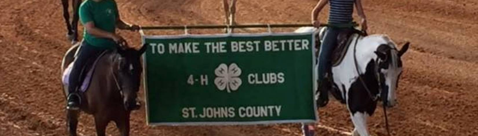Two youth riding their horses and carrying a 4-H banner at the Area B Horse Show