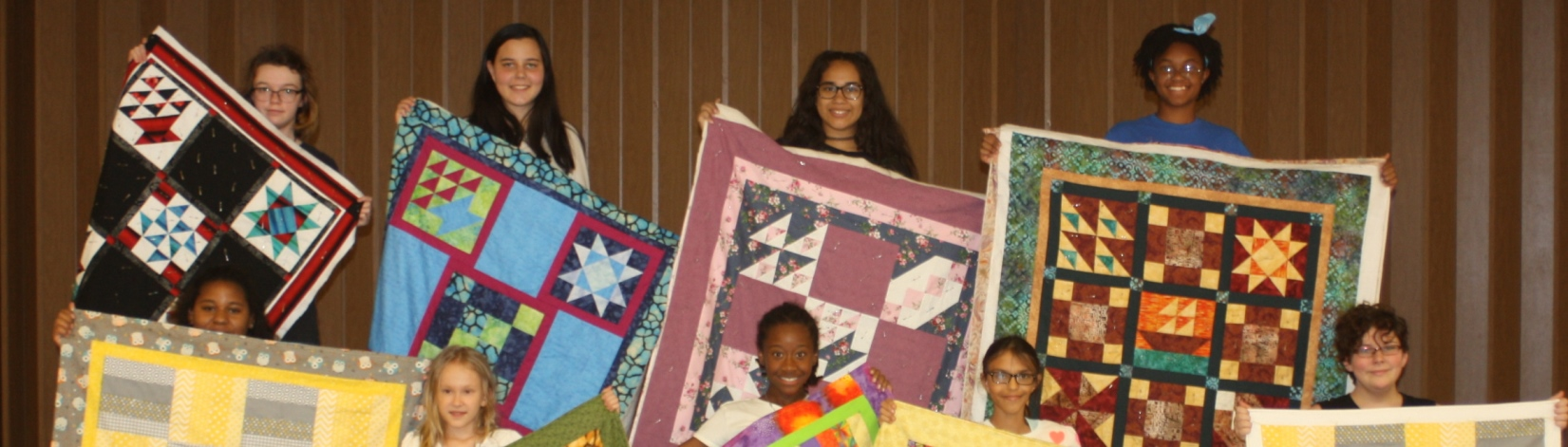 A group of 4-H youth holding pretty quilts they made at the 4-H Quilt Camp